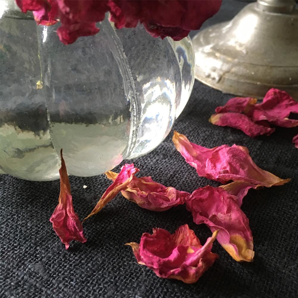 glasvas och fallende kronblad på svart linneduk
